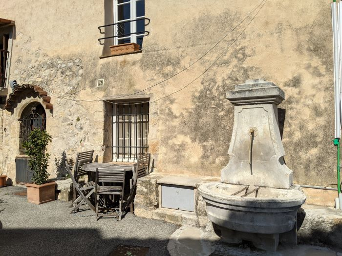 drinking fountain and table and chairs in French village square