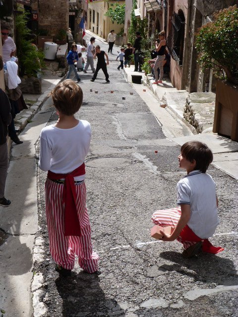 boys in traditional dress playing square boules