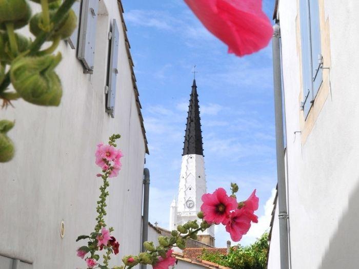 clock tower and flowers in Ars en Ré village in Île de Ré
